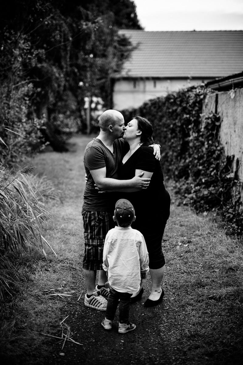Eltern küssen sich, Kind schaut zu