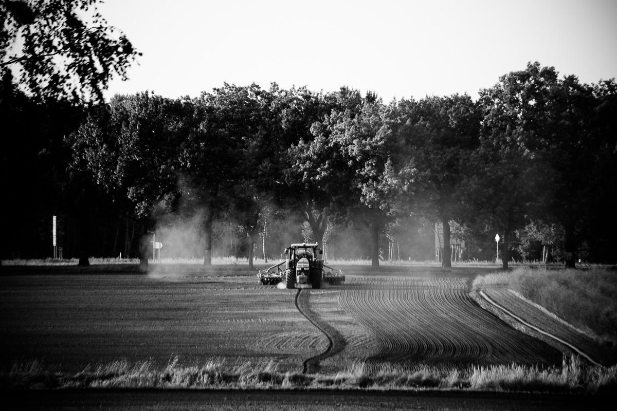 Ein Traktor pflügt das Feld in Schwarzweiss