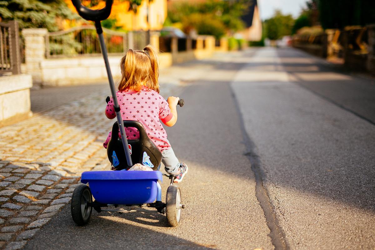 Mädchen sitzt auf Dreirad