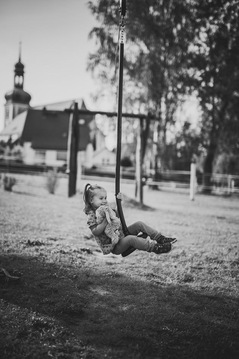 kleines Mädchen hängt an einer Seilbahn