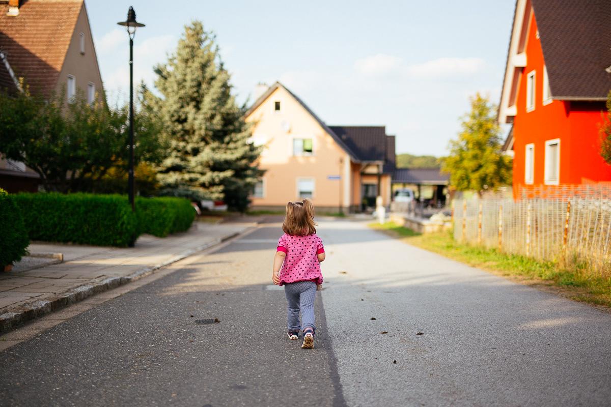 Kleines Mädchen läuft die Straße entlang
