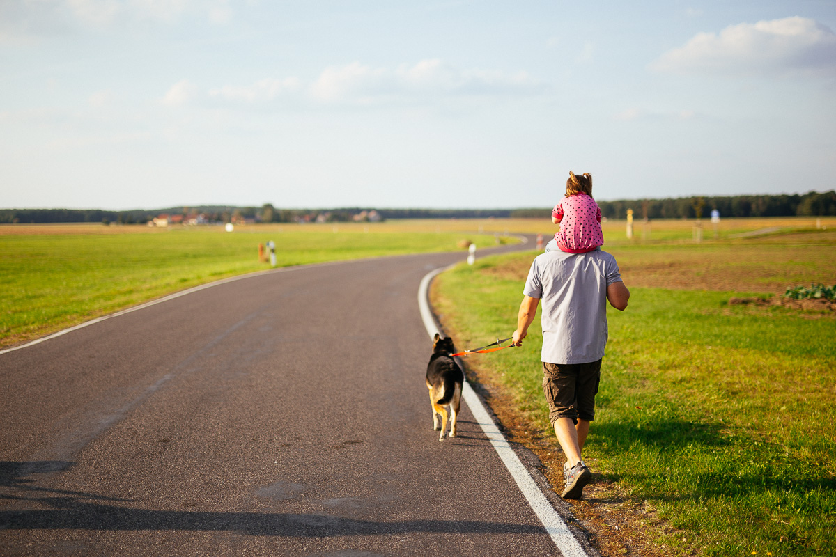 Papa mit Hund und Kind geht spazieren