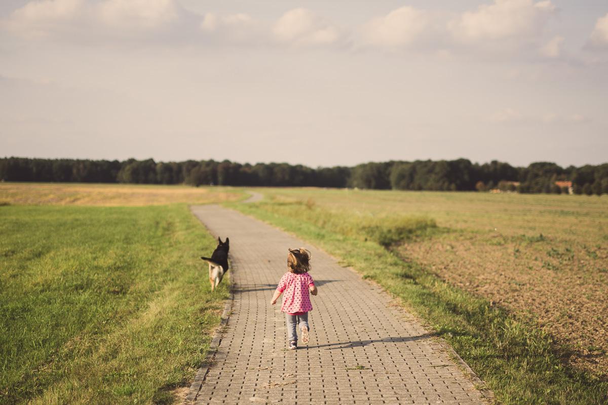 Kleines Kind rennt mit Hund um die Wette