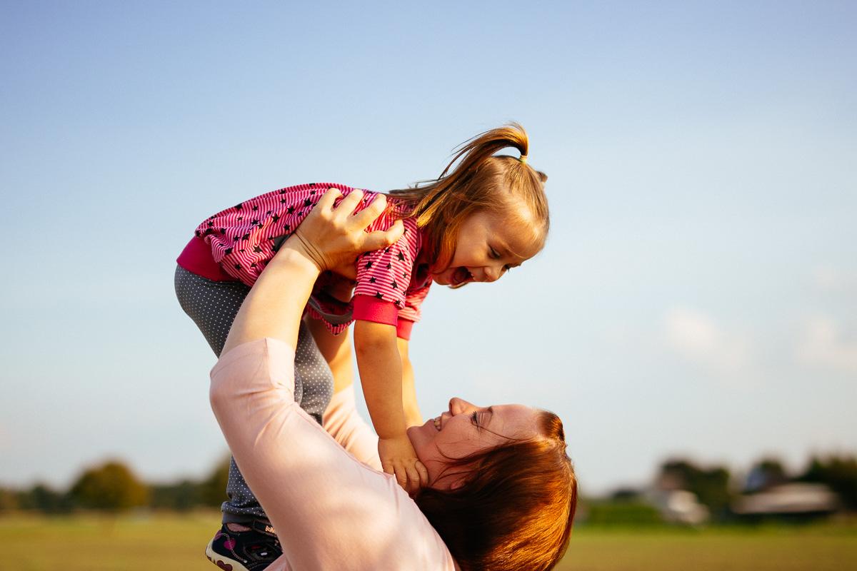 Kind wird von der Mutter in die Höhe gehoben