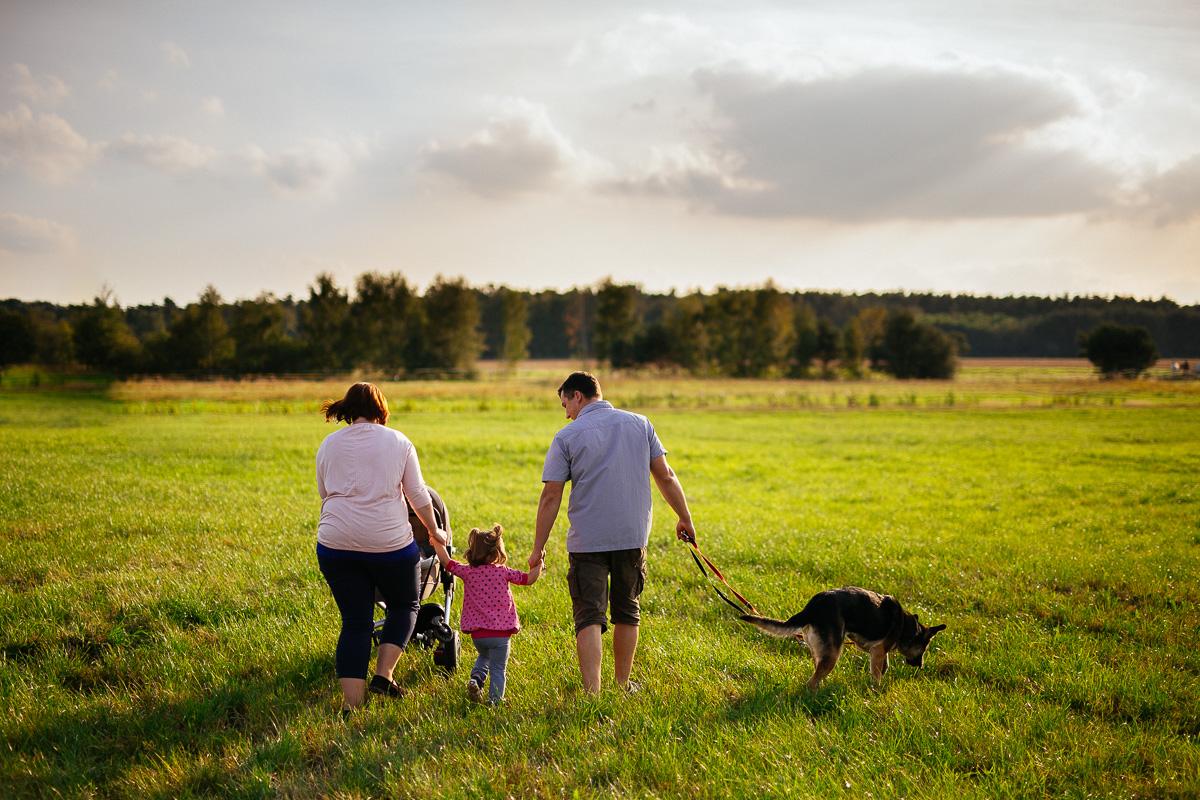 Familie mit Kindern und Hund geht auf einer Wiese spazieren