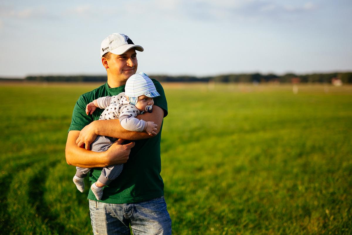 Vater hält seinen Sohn im Arm auf einer Wiese