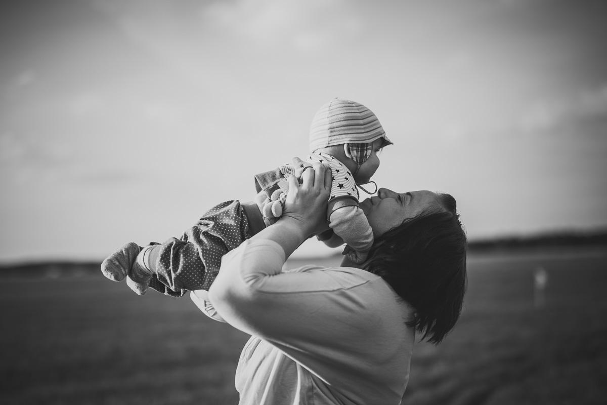 Mutter hebt ihren Sohn in die Luft