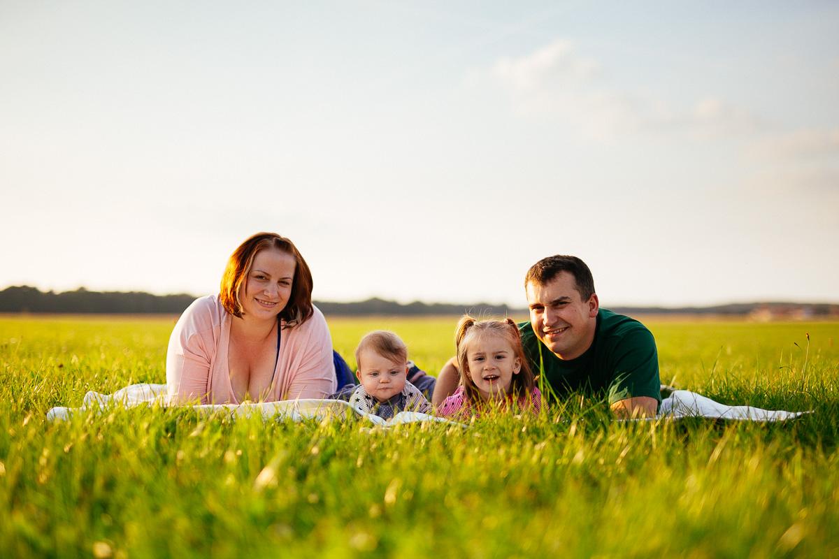 Familie mit zwei Kindern liegt auf einer Wiese