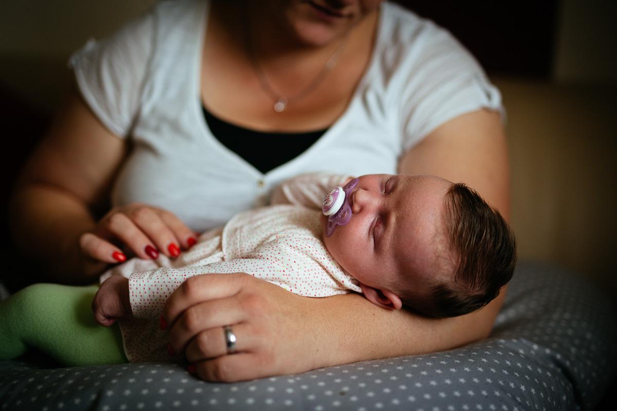 Baby schläft bei Mutter auf dem Arm