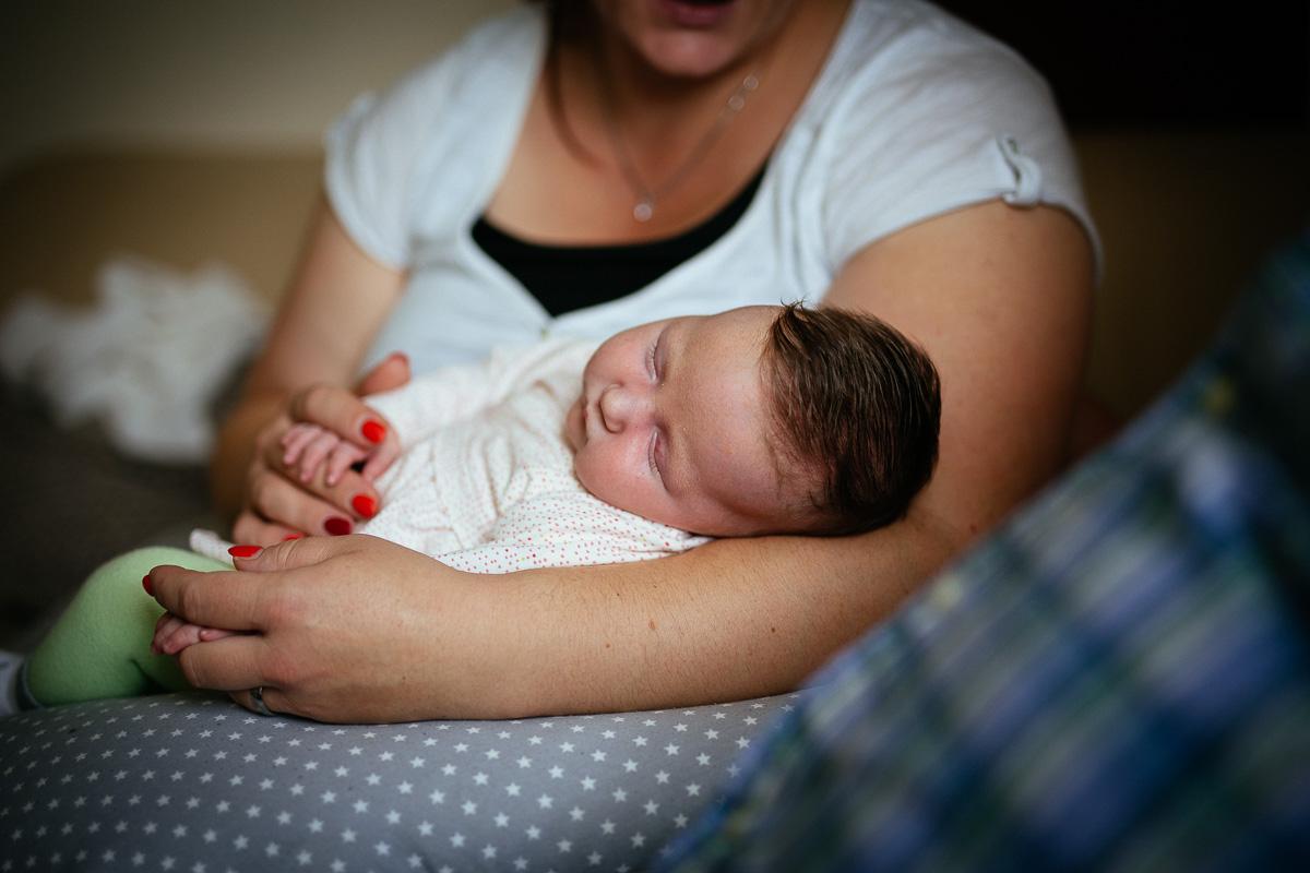 Baby schläft auf dem Arm der Mutter
