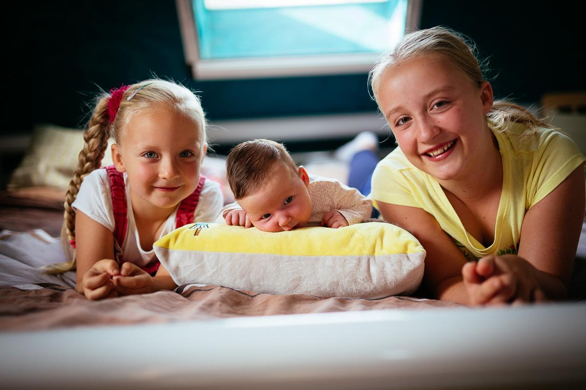 Drei Schwestern liegen auf dem Bett