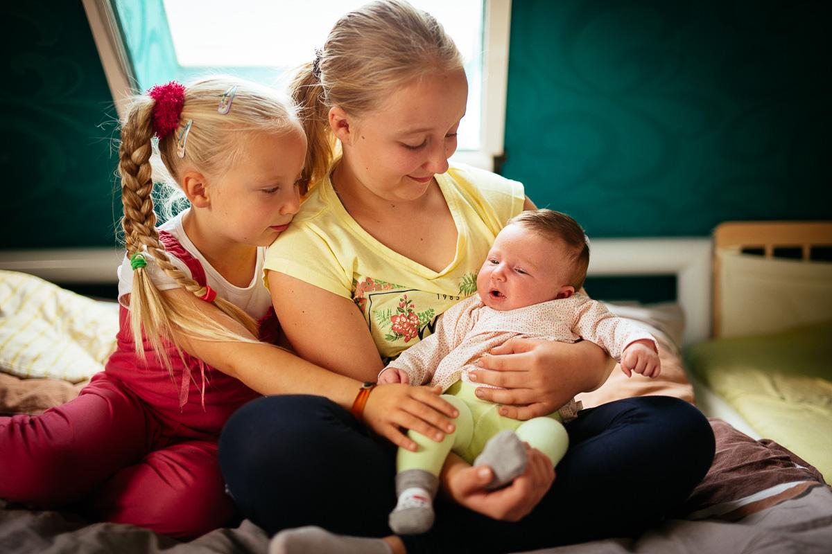 Zwei Mädchen halten ihre kleine Schwester auf dem Arm