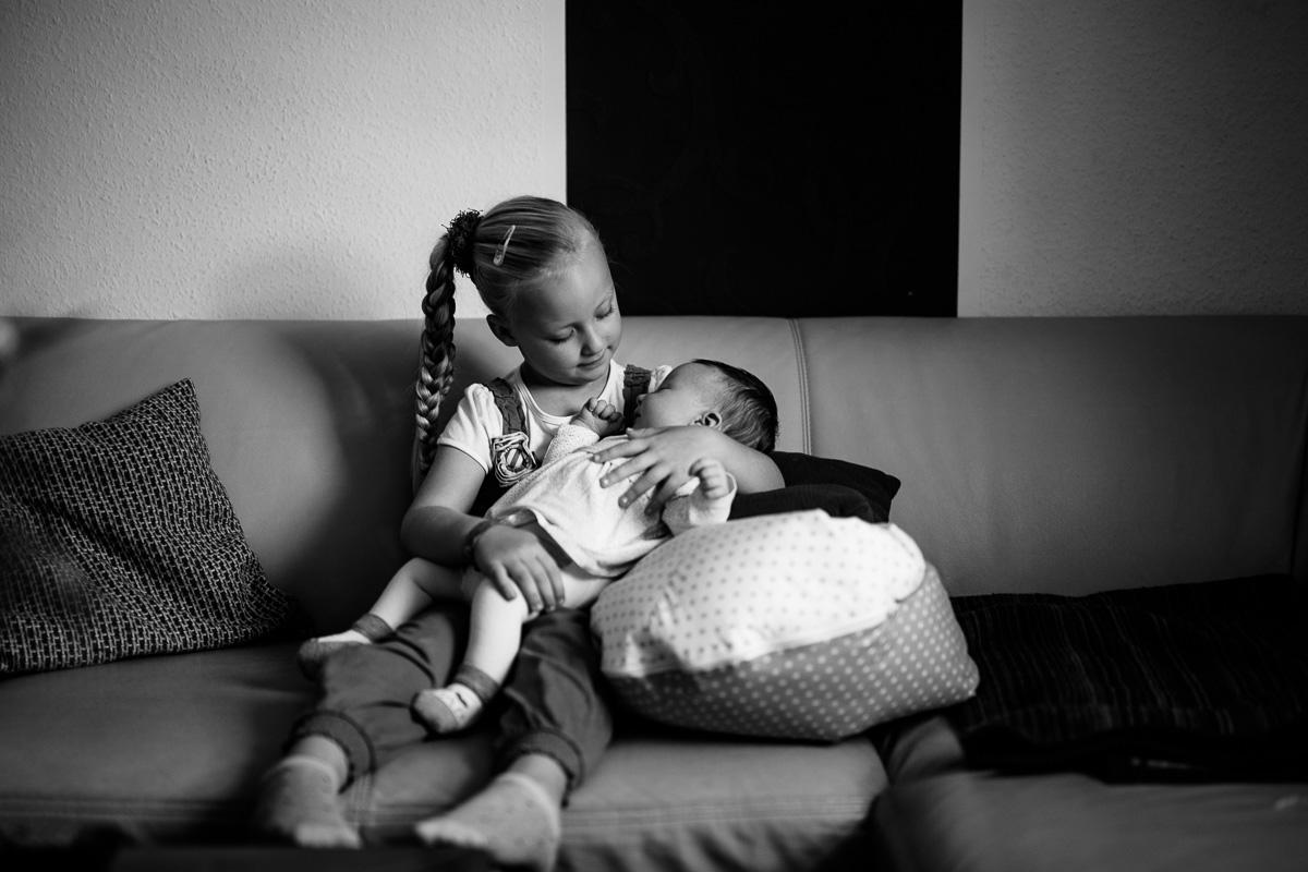 Mädchen hält ihre kleine Schwester im Arm