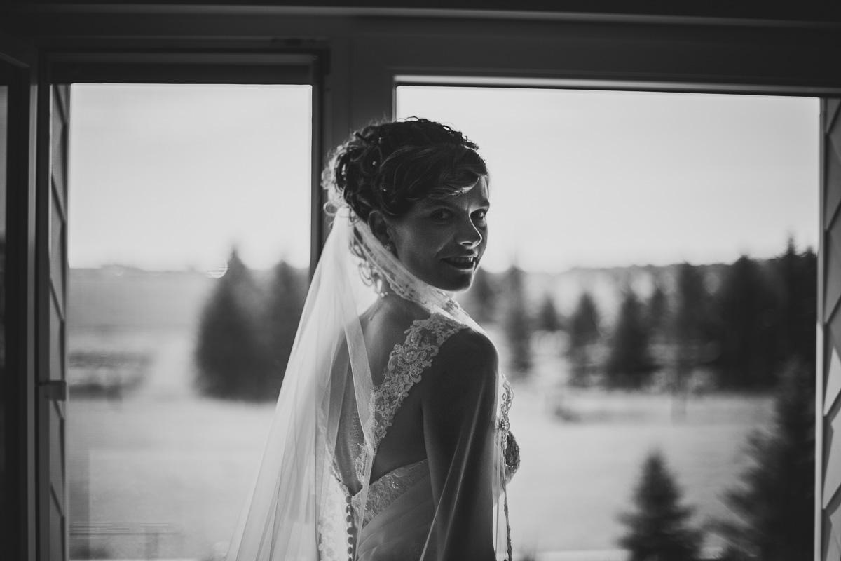 Braut steht vor dem Fenster im Gegenlicht