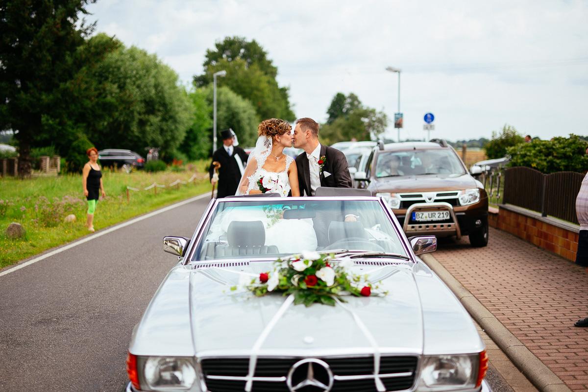 Brautpaar küsst sich im Mercedes Cabrio Brautauto