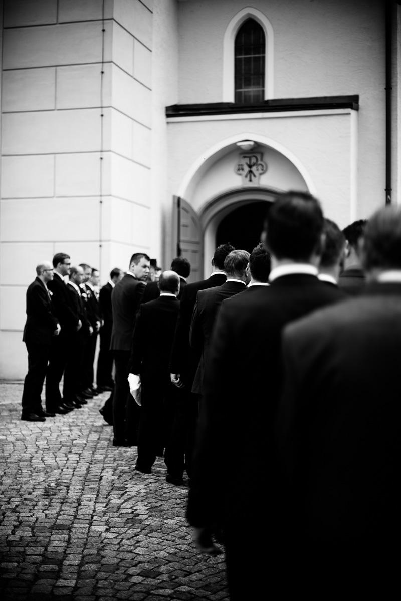 Männer warten vor der Kirche