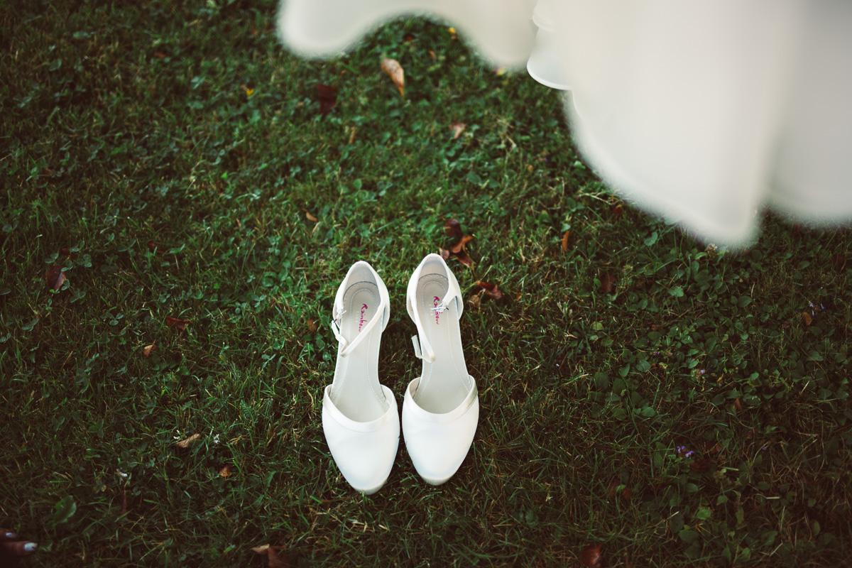 Brautschuhe stehen unter hängendem Brautkleid
