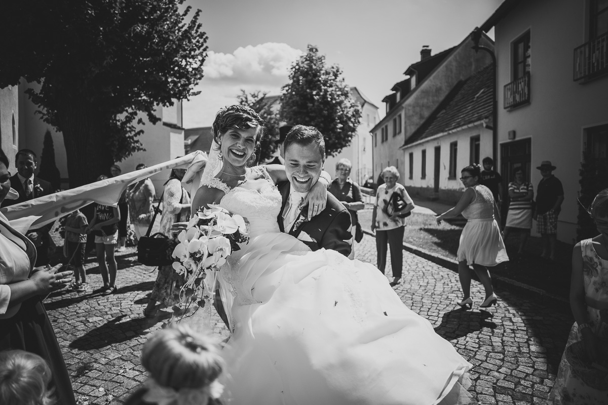 Braut wird vom Bräutigam durch Bettlaken getragen