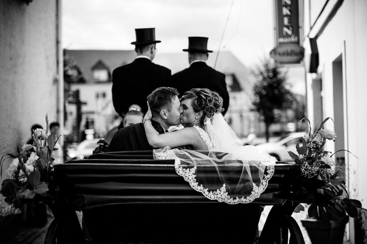 Brautpaar küsst sich in der Pferdekutsche