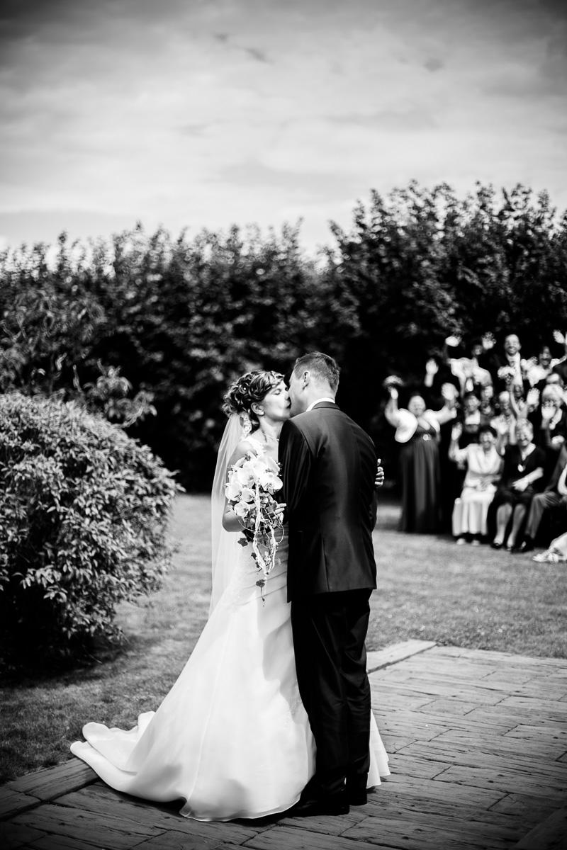 Brautpaar küsst sich vor Hochzeitsgesellschaft