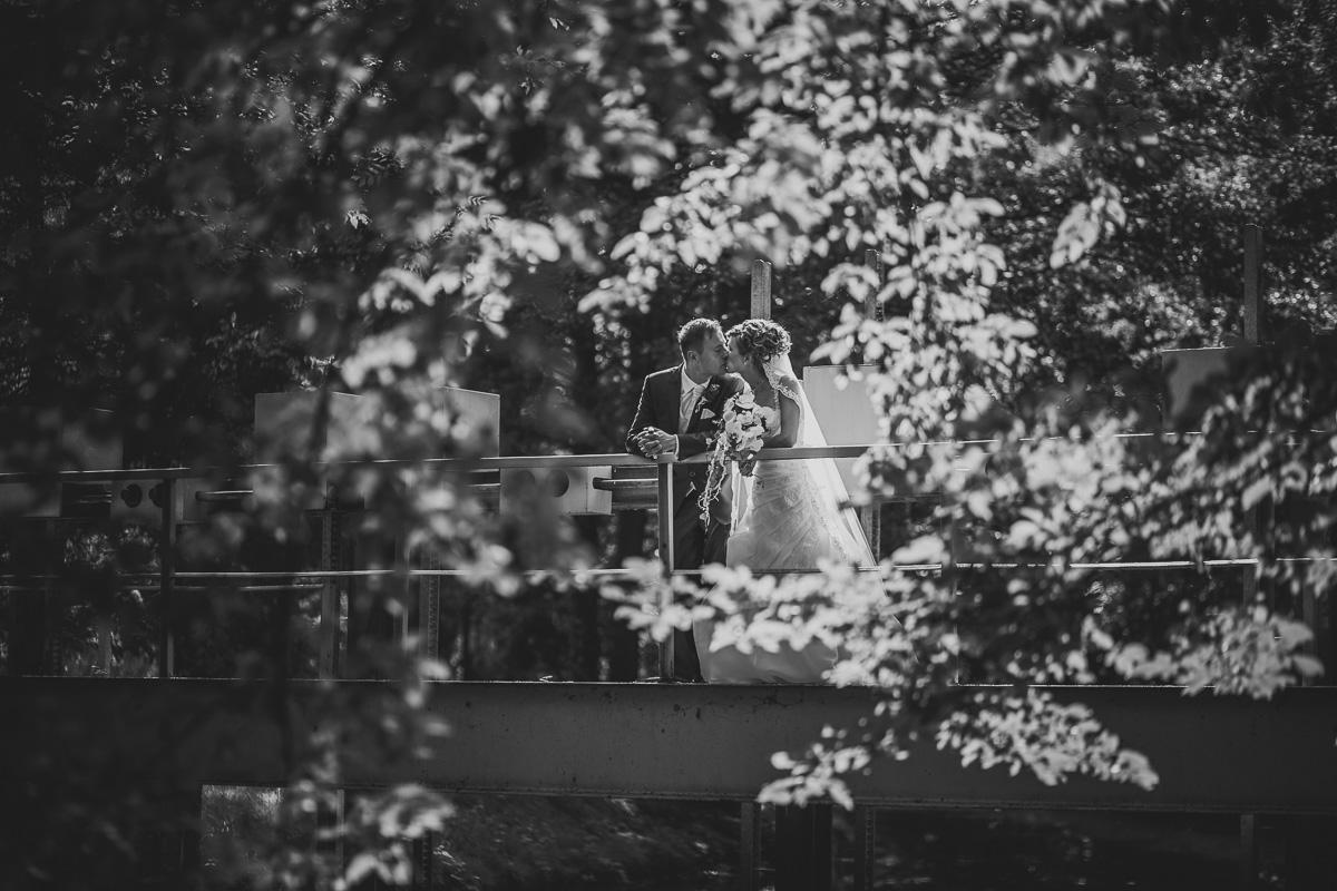 Brautpaar küsst sich auf Brücke