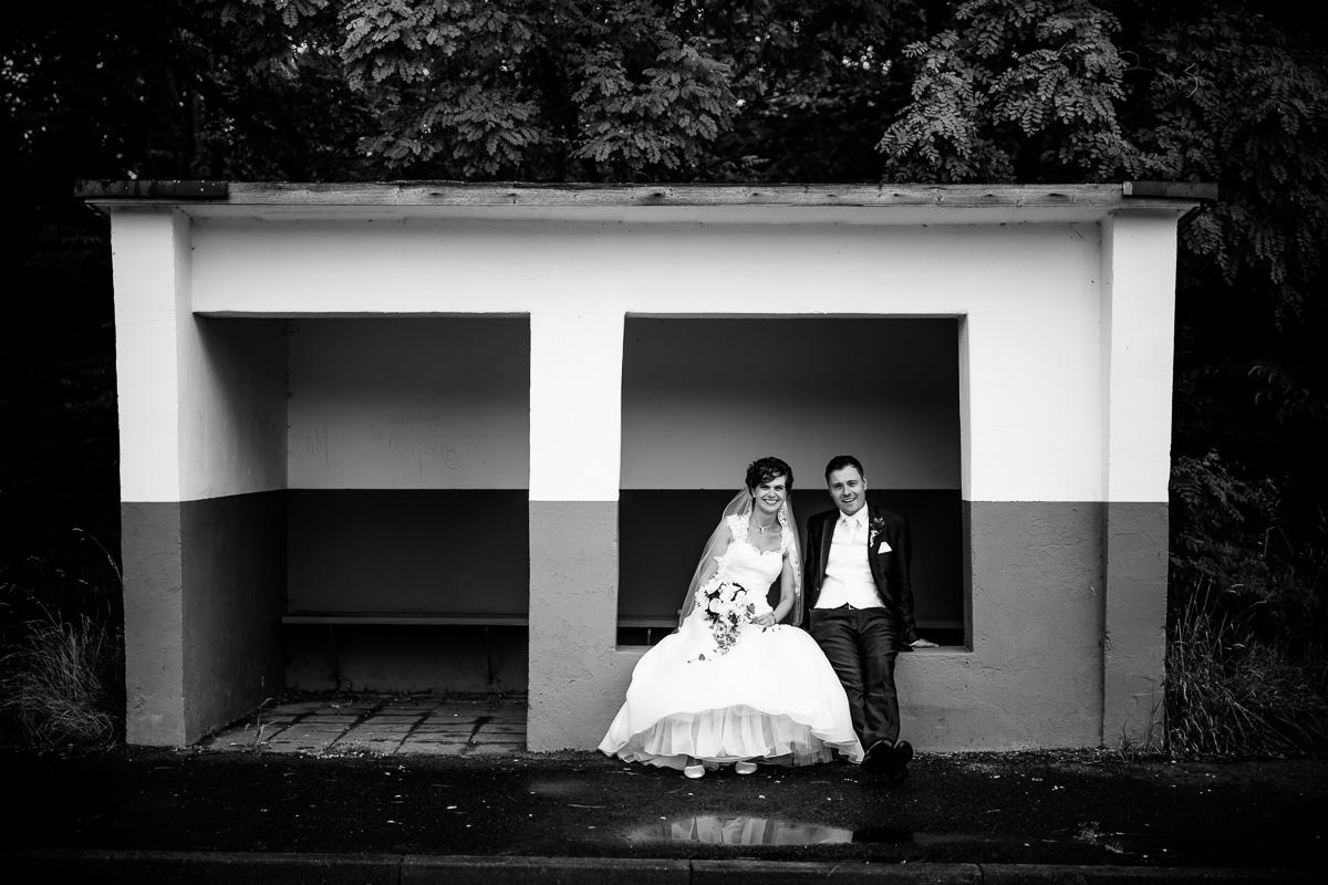 Brautpaar sitzt in der Bushaltestelle