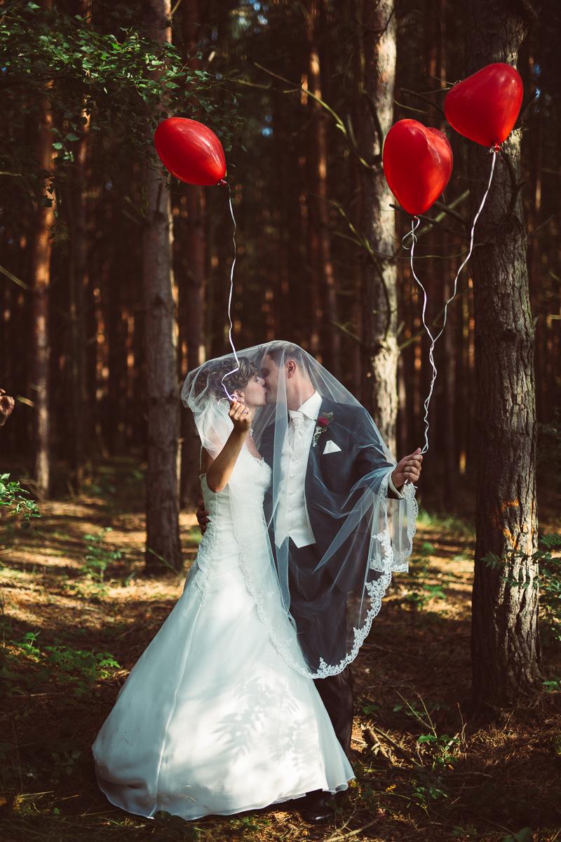 Brautpaar küsst sich mit Luftbalons in der Hand im Wald