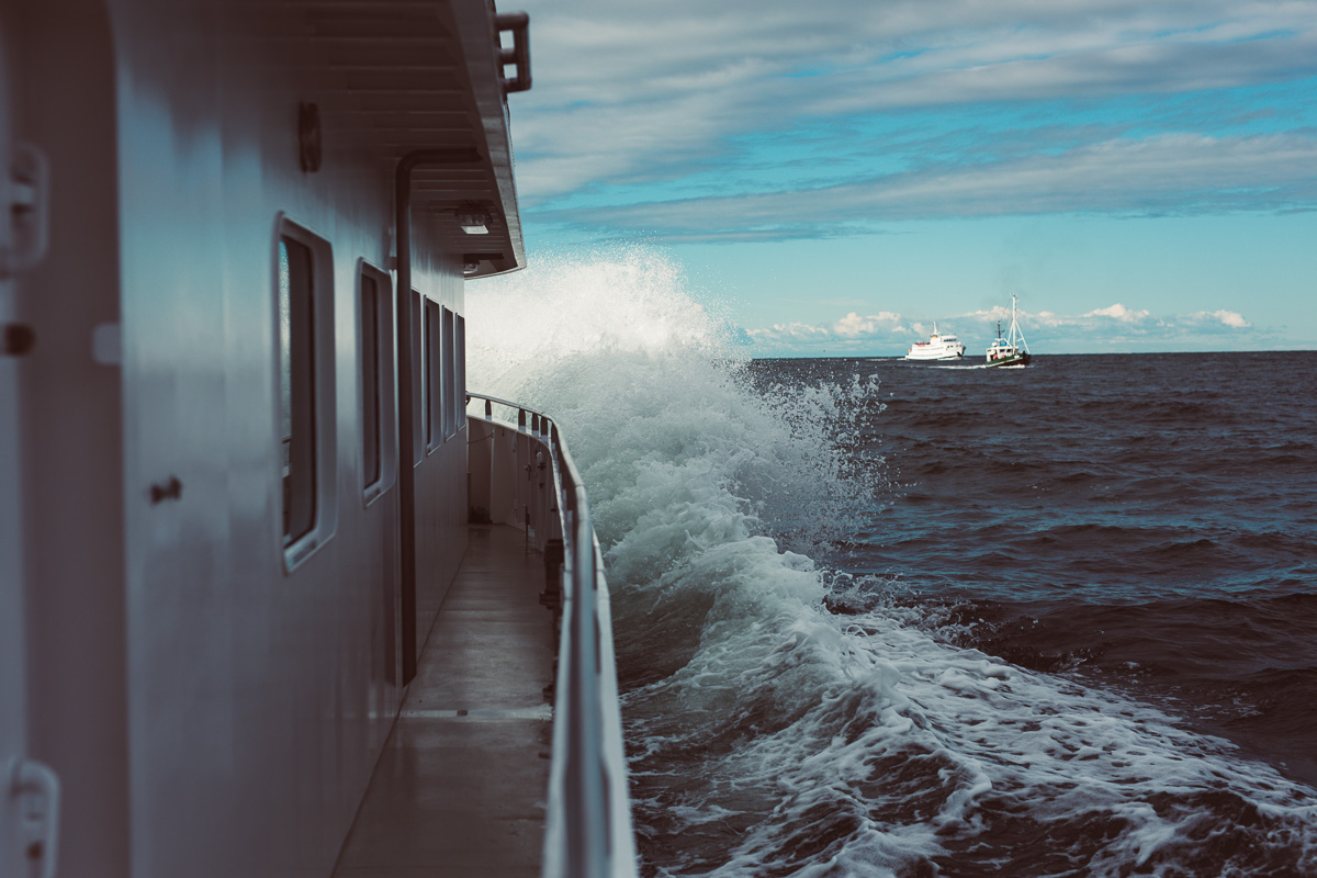 Welle bricht am Schiffsbug vor dem Kreidefelsen auf Rügen