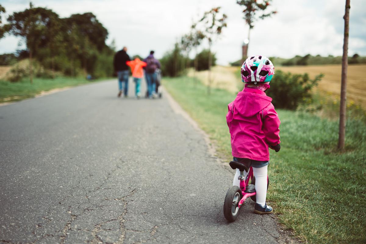 Ein Mädchen mit Laufred steht am Straßenrand