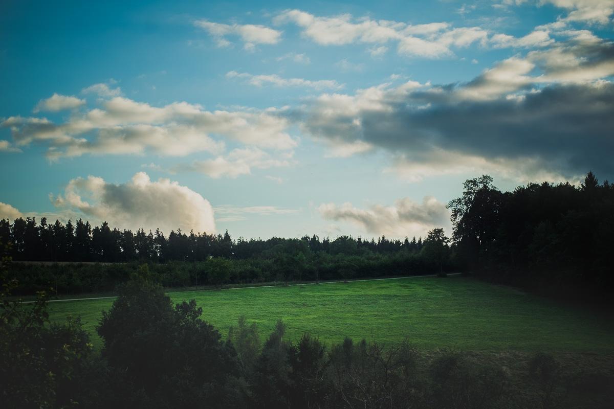 Grüne Wiese und blauer Himmel mit Wolken