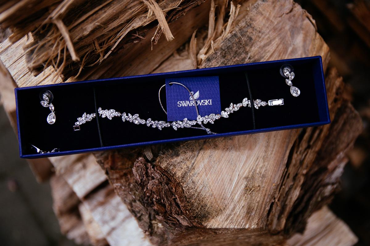 Brautschmuck von Swarovski liegt auf einem Baumstumpf
