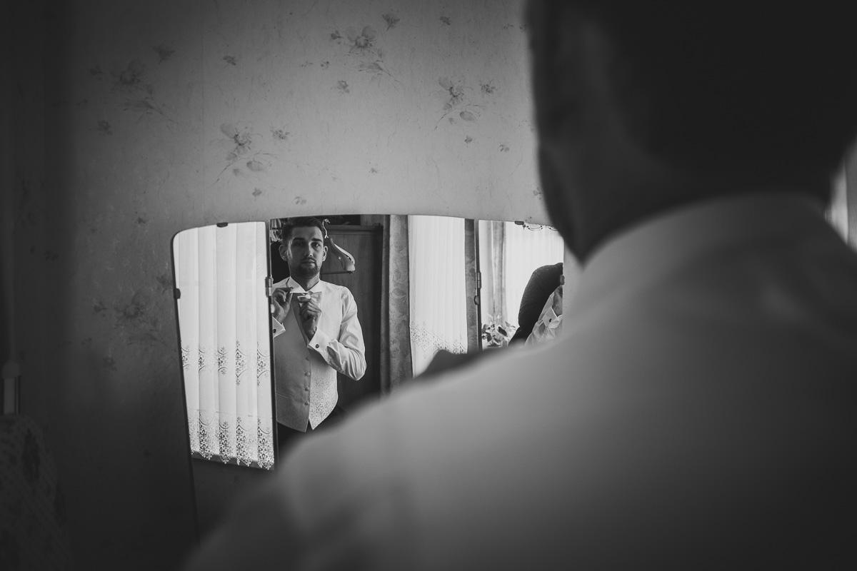 Bräutigam richtet seine Fliege im Spiegel