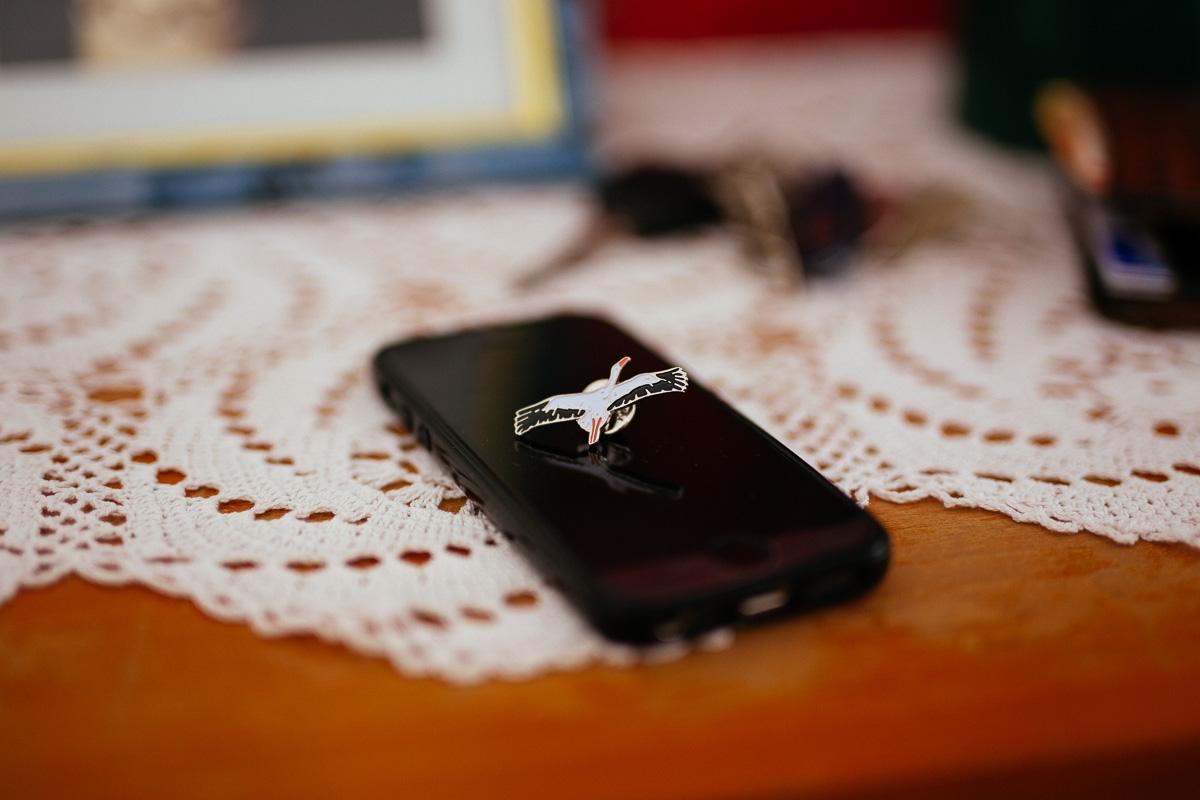 Storch Anstecker liegt auf einem iPhone