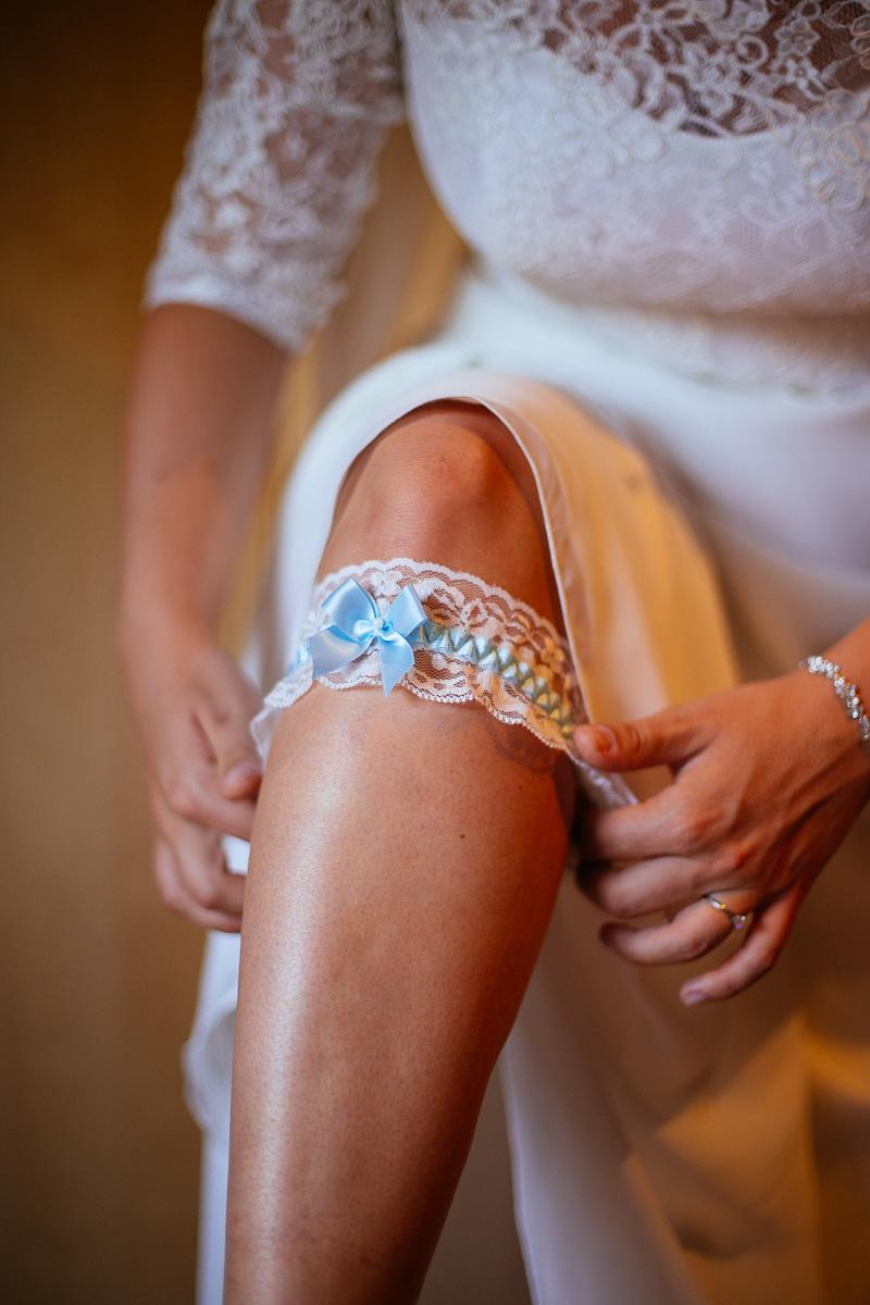 Braut zieht blaues Strumpfband hoch