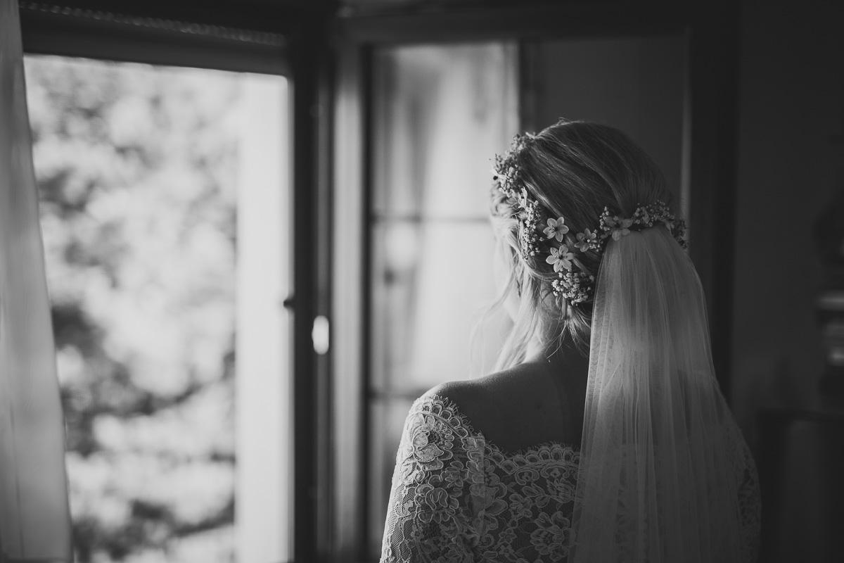 Braut mit Blumen in den Haaren schaut aus dem Fenster