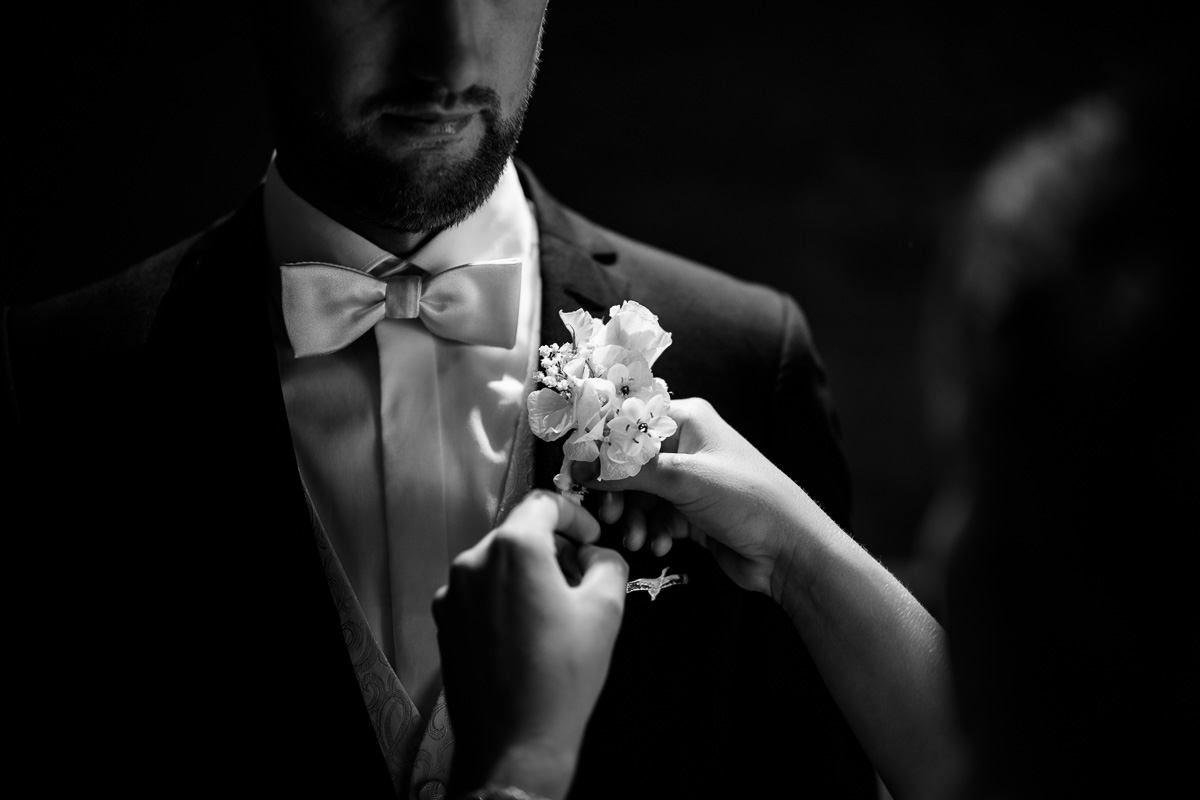 Blumengesteck wird von der Braut beim Bräutigam angebracht