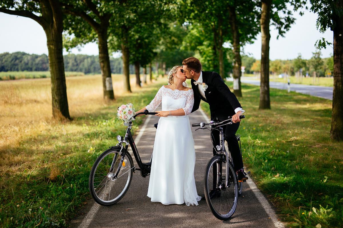 Brautpaar mit Fahrrädern küsst sich
