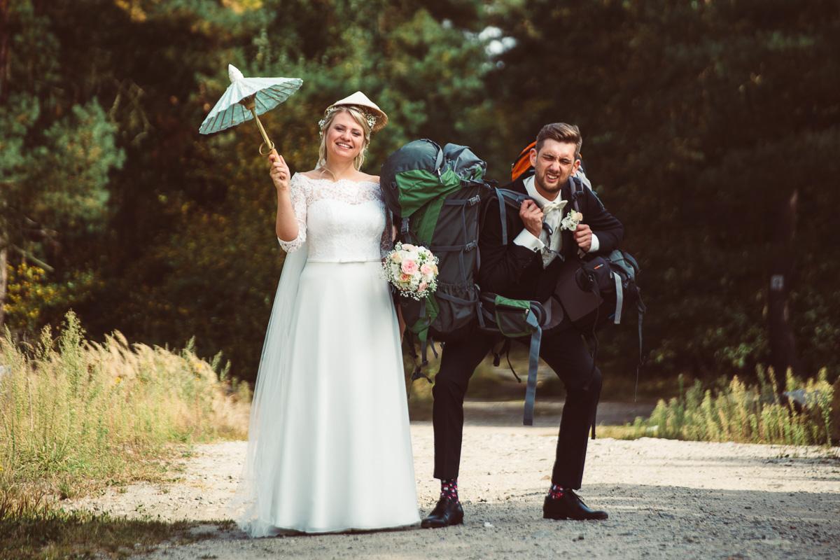 Brautpaar mit Wanderrucksäcken und chinesischem Schirmchen