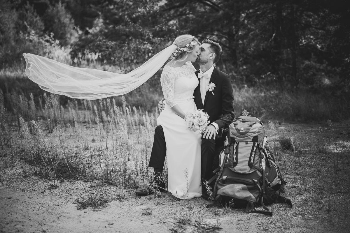 Braut und Bräutigam küssen sich beim Wandern mit Schleier im W