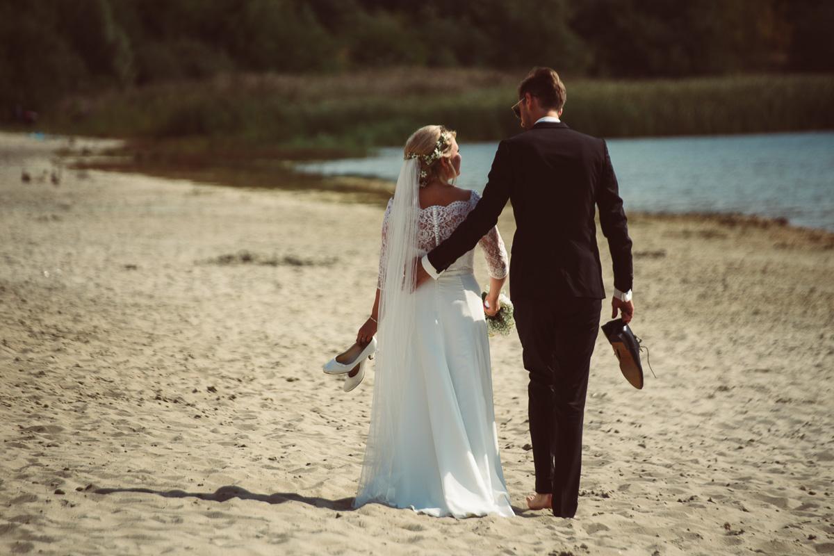 Brautpaar schlendert am Strand entlang