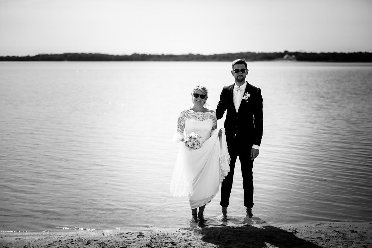 Brautpaar mit Sonnenbrillen steht am Strand