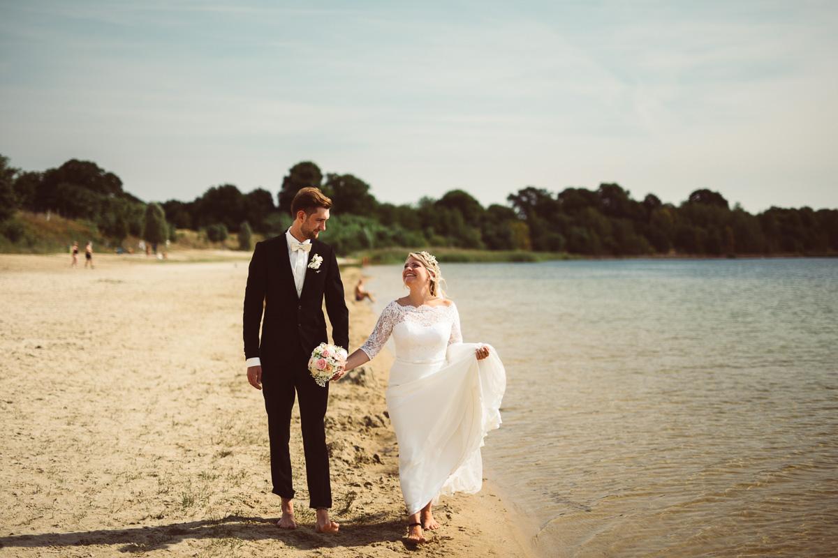 Brautpaar schlendert verliebt am Strand entlang