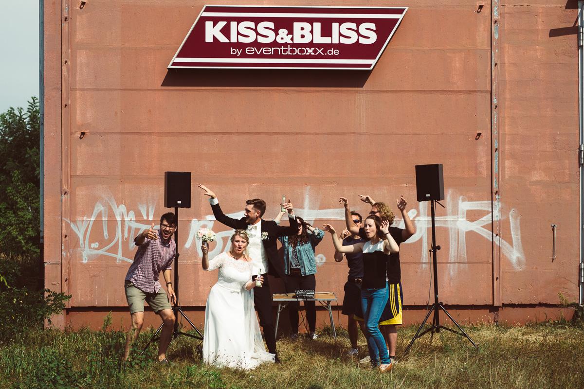 Brautpaar und Freunde tanzen vor einer Disco