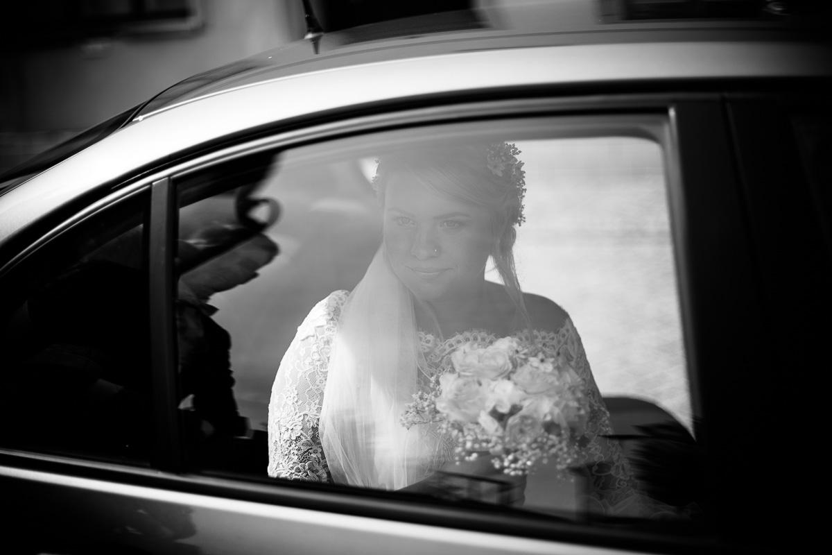 Braut schaut erwartungsvoll aus dem Brautauto