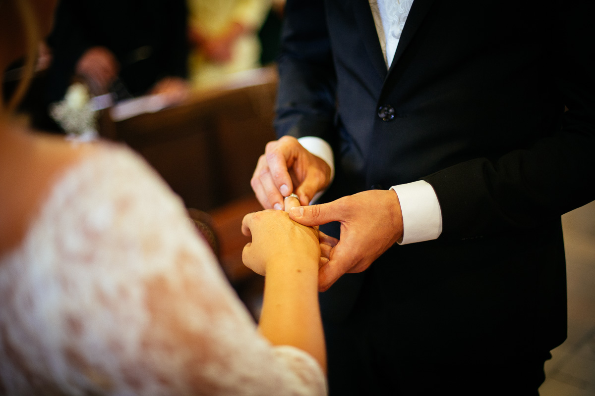 Bräutigam steckt der Braut den Ring an