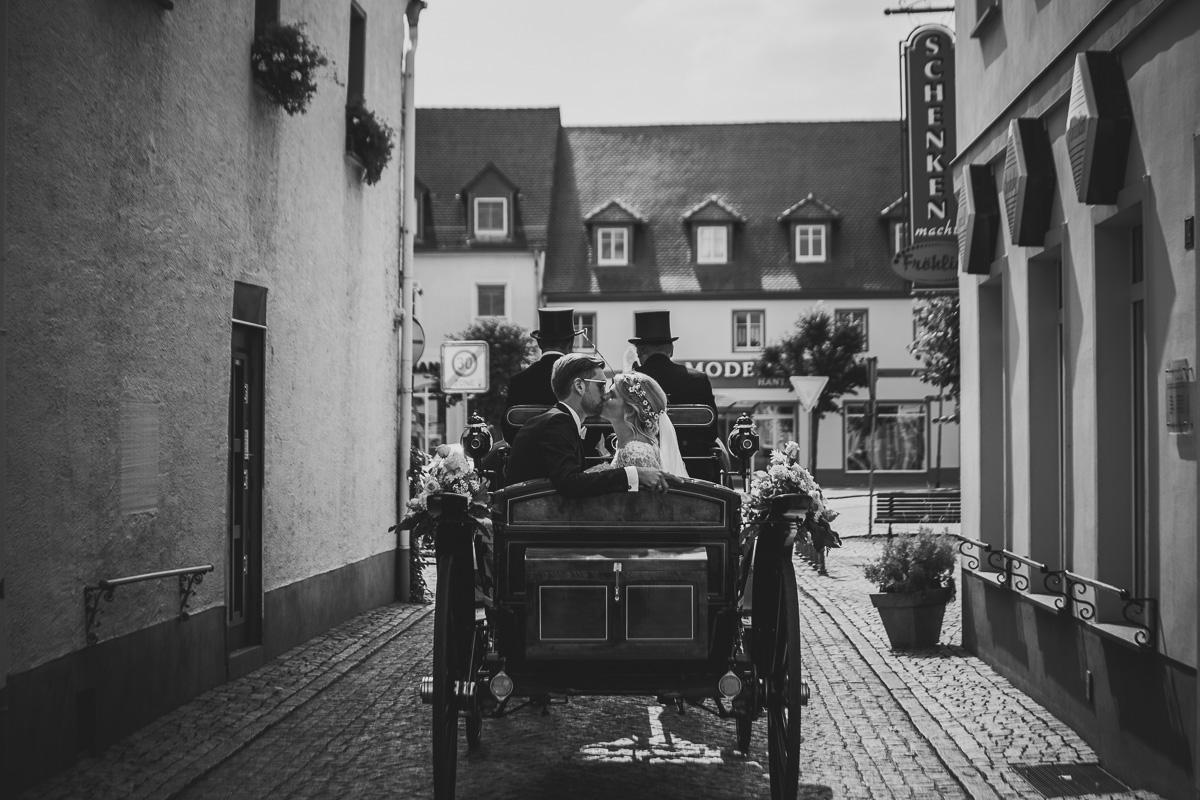 Brautpaar küsst sich in der Kutsche