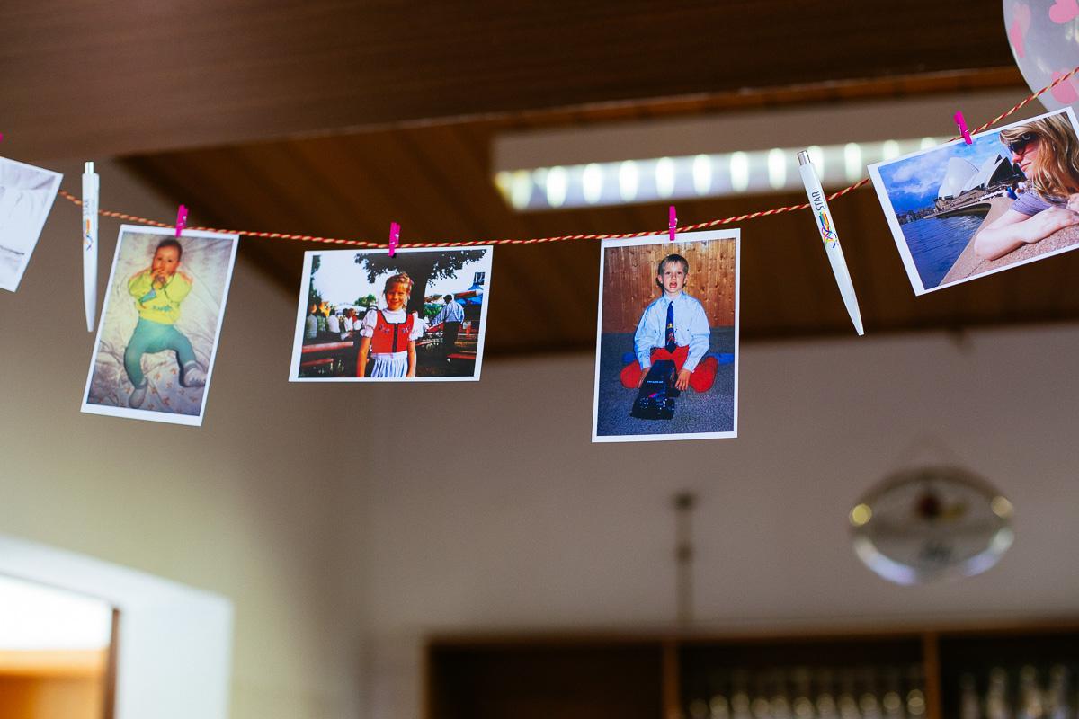 Kinderfotos des Brautpaares hängen im Saal an der Bar