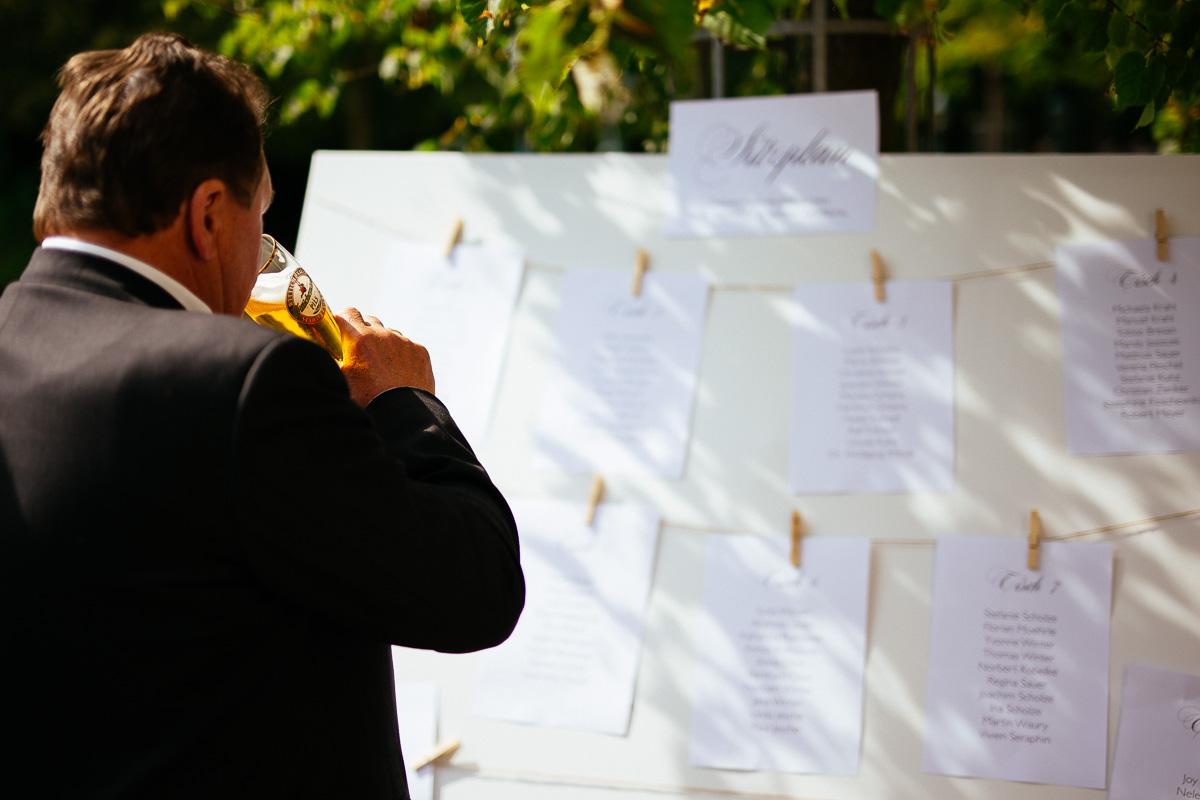 Gast mit Bier in der Hand betrachtet den Sitzplan der Hochzeit