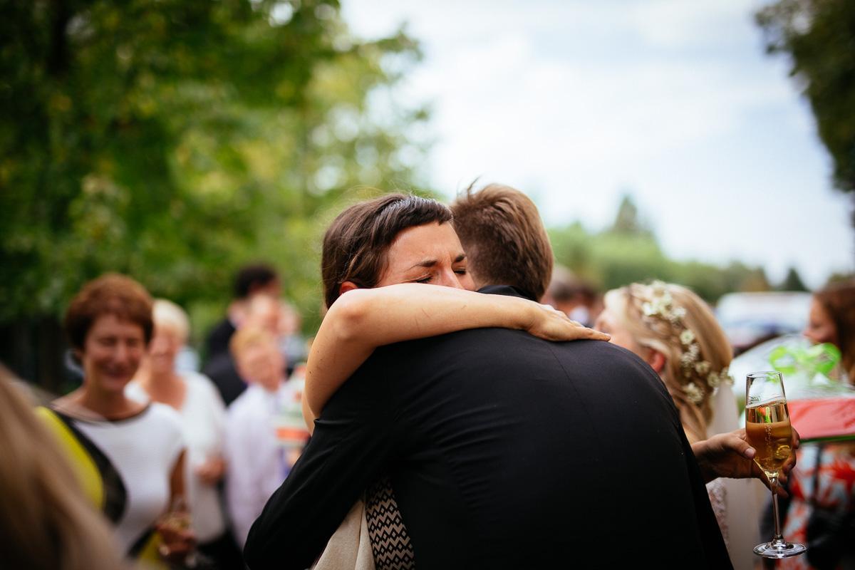 Freundin umarmt Bräutigam bei der Gratulation und weint