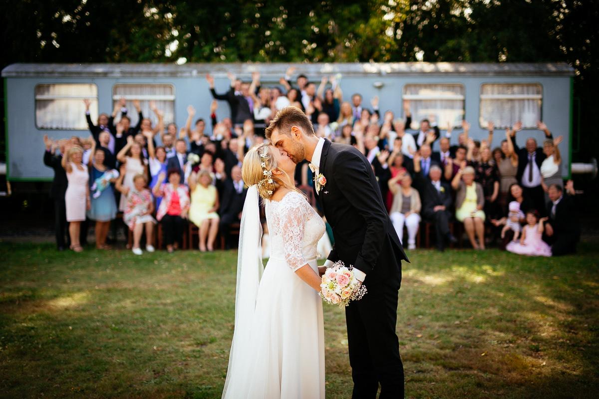 Brautpaar küsst sich vor den Gästen